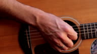 Acoustic guitar playing chords, close-up moving from body up neck video