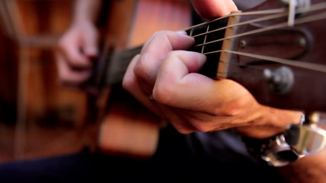 Acoustic guitarist playing chords, close-up moving from body up neck. video