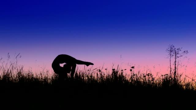 Acrobat girl exercising in the evening field. Scorpio position video