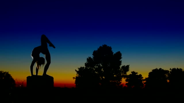 Acrobat girl exercising on column in the evening  Arrow position video