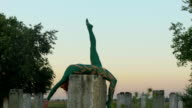 Acrobat lying at concrete column with leg rised up video