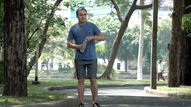 Active athletic young man runner jogging in park. Fit male sport fitness training. Drinking water video