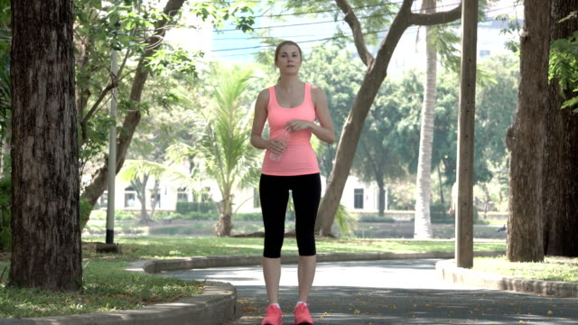 Active athletic young woman runner jogging in park. Fit female sport fitness training. Drinking water video