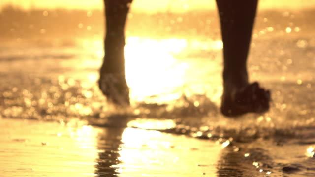 SLOW MOTION CLOSEUP LENS FLARE Active man running on beach splashing ocean water video