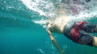UNDERWATER: Active man with tattoo swimming and relaxing in crystal clear ocean video