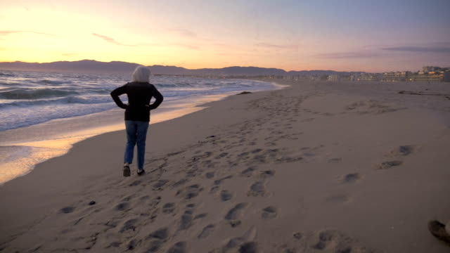 Active mature fit woman walking on beach during sunset turning to face camera video