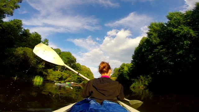 Active rest, young girl paddling boat on river, vacation, travel video
