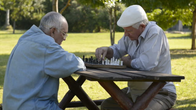 Active retirement and free time, four elderly men playing chess video