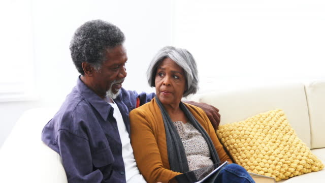 Active Senior African American Couple Reading Together on the Sofa video