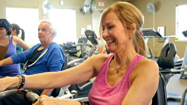 Active senior Caucasian woman riding recumbent bicycle in gym video