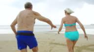 Active senior couple on beach in swimwear running towards sea video