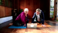 Active senior couple watch exercise video on laptop video