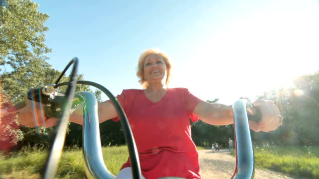 Active senior woman riding bicycle against the sun smiling video
