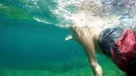 UNDERWATER: Active young man with tattoo swimming above rocky sea floor in ocean video