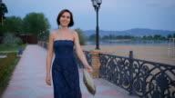 Active young woman is walking briskly, in the hands of her handbag golden brown video