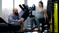 Active young woman training in gym, talking to handsome sportive man, high five video