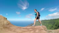 Active young woman walking on path along the mountain ridge with stunning views video