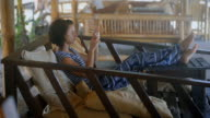Activities on the island of Bali. A girl with short hair in a striped T-shirt and baggy trousers sitting in an easy chair, put his feet on the table. It relaxes and relieves beautiful views on your phone video