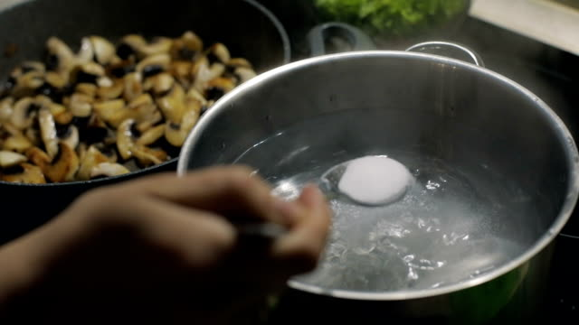 Add a salt to boiling water in pot. Pan with fried mushrooms in background. Slow motion video