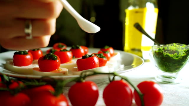 Adding balsamic vinegar to cheese and tomato salad (Caprese). Part of the set video