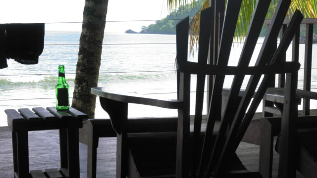 Adirondack chair and empty beer bottle on stool at a tourist resort and sea viewed from tourist resort, Trinidad, Trinidad and Tobago video