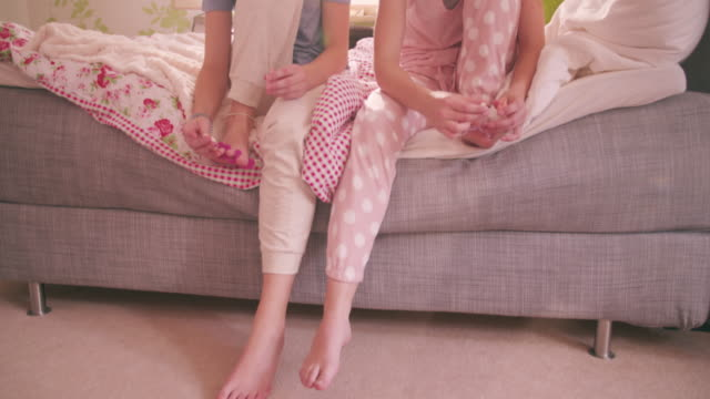 Adolescent girls in pyjamas on bed painting their toenails together video