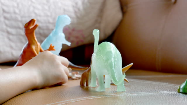 Adorable asian girl playing with plastic dinosaurs video
