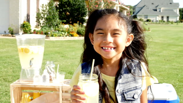 Adorable Asian little girl smiling in front of lemonade stand video