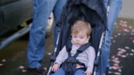 Adorable baby boy being pushed in a stroller, on a walk with his parents video