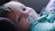 Adorable baby boy laying on a changing table with a pacifier in his mouth, looking up video