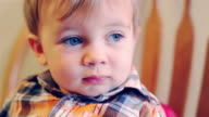 Adorable baby boy looking off into the distance and then smiling video