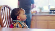 Adorable baby boy sitting in a booster seat wearing a bib, and his mom gets him ready to eat video