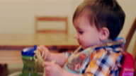 Adorable baby boy sitting in a high chair booster seat and eating spaghetti with his hands video