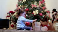 adorable baby girl stacking containers and playing with them under a christmas tree video