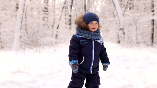 Adorable boy dancing and having fun in snowy park. video