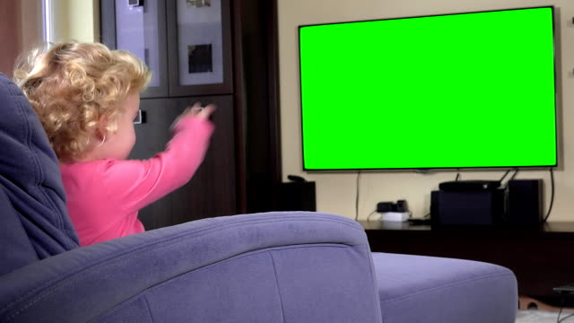 Adorable child looking at tv and dancing moving hands. Green chroma key screen video