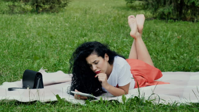 Adorable curly girl relax on plaid in park with tablet video