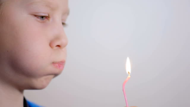 Adorable eight year old boy blowing candle indoor. Slow motion video