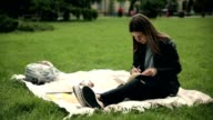 Adorable female student reading tutorial outdoors. video