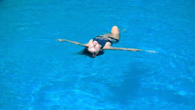 Adorable fit woman in black swimsuit is relaxing luying on the water. Young shapely girl is showing comfort and pleasure floating in the swimming pool video