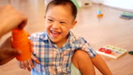 Adorable Hispanic boy with Down's Syndrome laughs as he teacher blows bubbles video