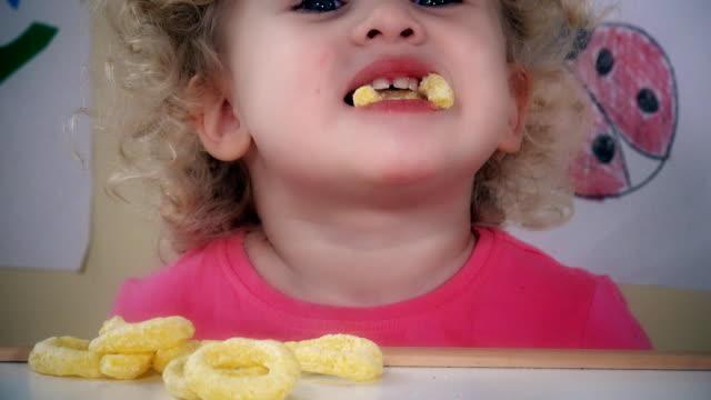 Adorable kid eating corn circle sticks video