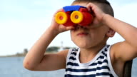 adorable kid in striped shirt looking through binoculars in front of the sea horizon video