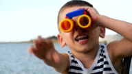 adorable kid in striped shirt looking through binoculars in front of the sea horizon waving with hand video