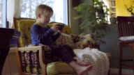 Adorable kid sits on living room couch and plays on a phone video