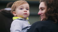 Adorable little boy being held by his mom, and they walk toward their garage video