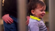 Adorable little boy climbing onto a play structure with a big smile on his face video