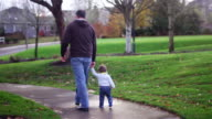 Adorable little boy holding his dad's hand while walking in a park, mom following with a stroller video