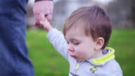 Adorable little boy holding his dad's hand while walking in a park, then looking behind him video