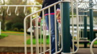 Adorable little boy holding his mom's hand and walking down the steps of a play structure video